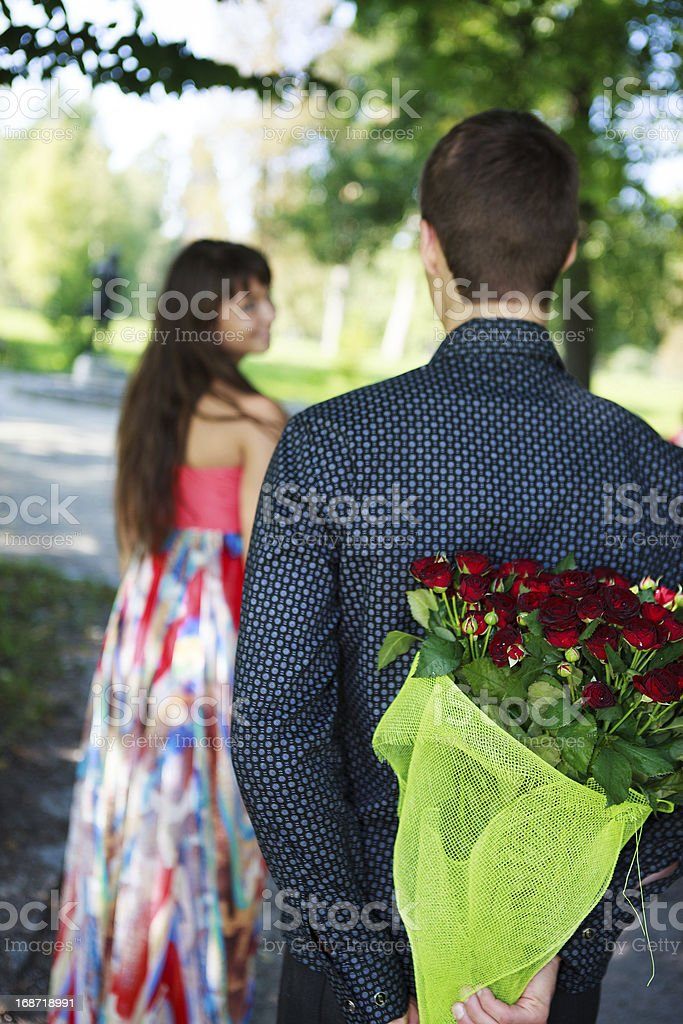 Young man keeps behind his back a bouquet of roses royalty-free stock photo