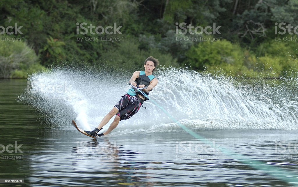 young man kicking up spray on water ski royalty-free stock photo