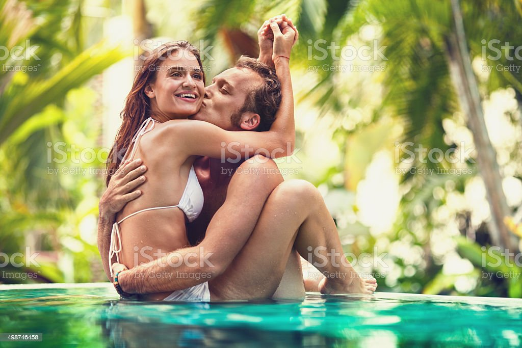 Young man kissing hid girlfriend in infinity pool. stock photo