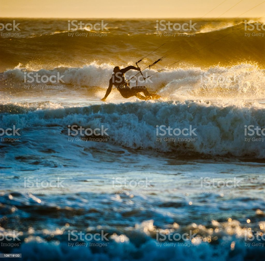 Young Man Kite Boarding in Ocean Waves at Sunset stock photo