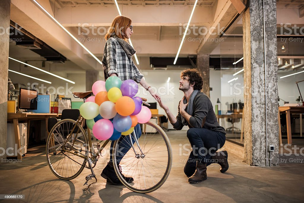 Young man kneeling and proposing his girlfriend. stock photo