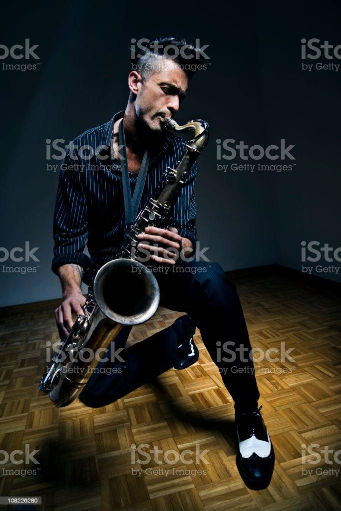 Young Man Kneeling on Floor Playing Saxophone stock photo