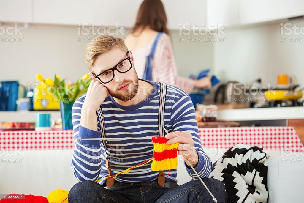 Young man knitting stock photo