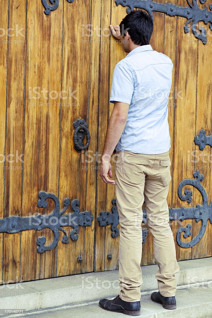 Young man knocking on closed wooden church door. stock photo