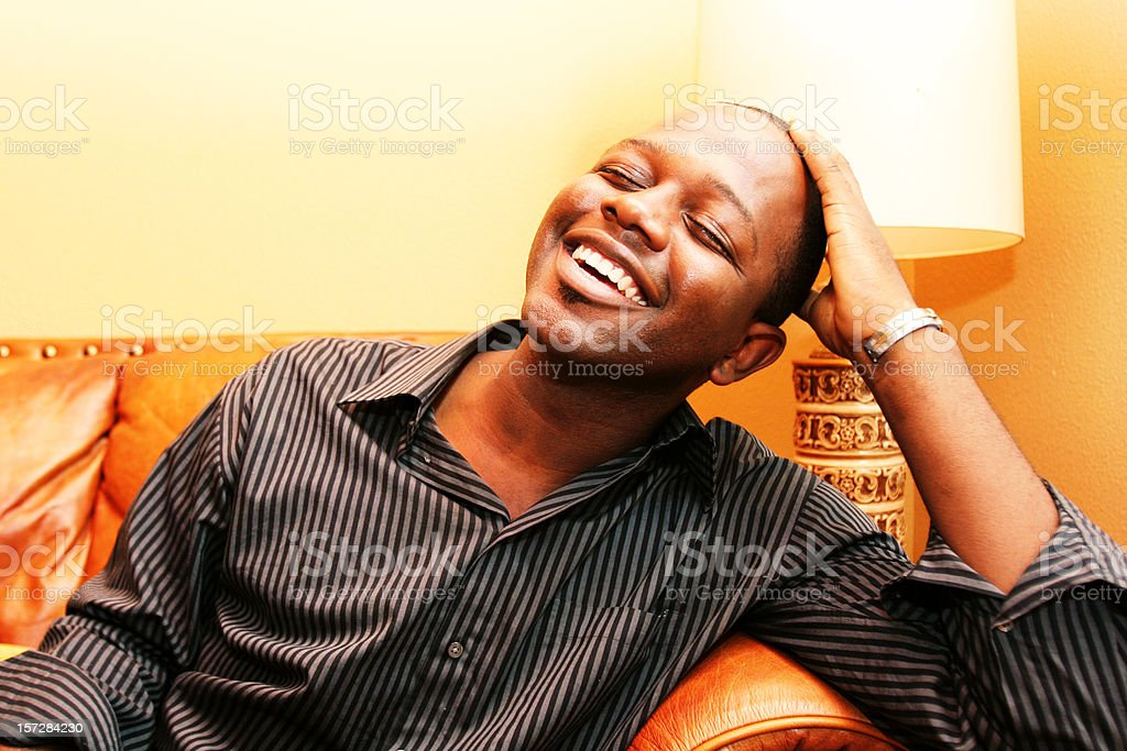 Young Man Laughing on a Couch stock photo