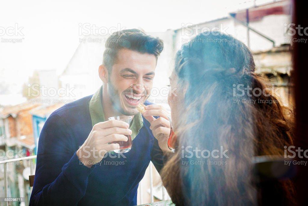 Young man laughing while enjoying tea wih girlfriend stock photo