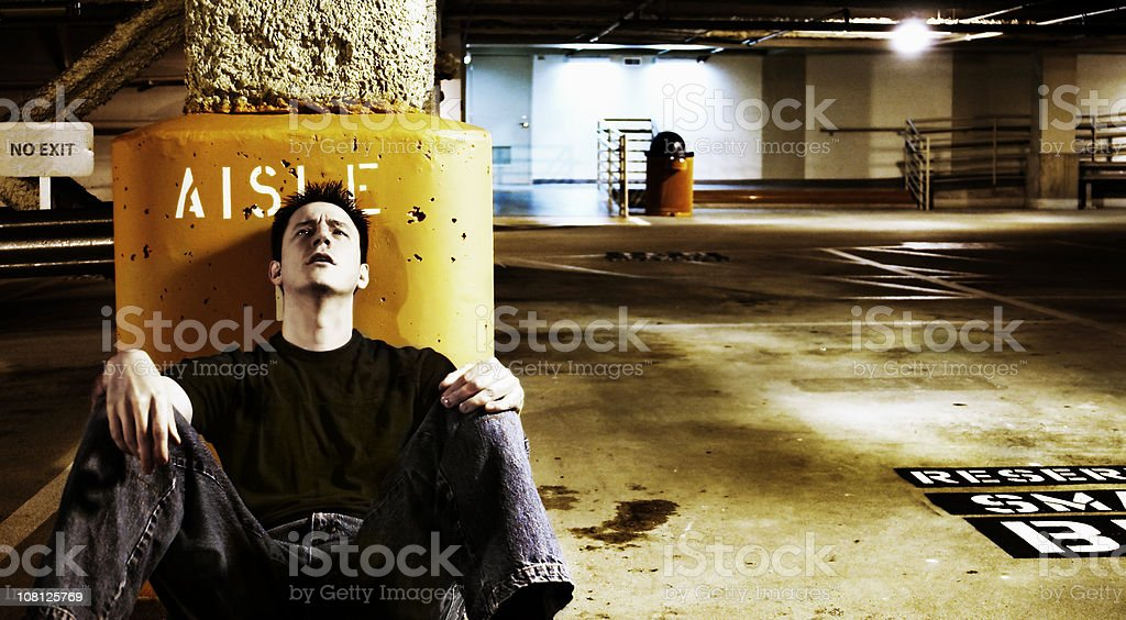 Young Man Leaning Against Column in Parking Garage royalty-free stock photo