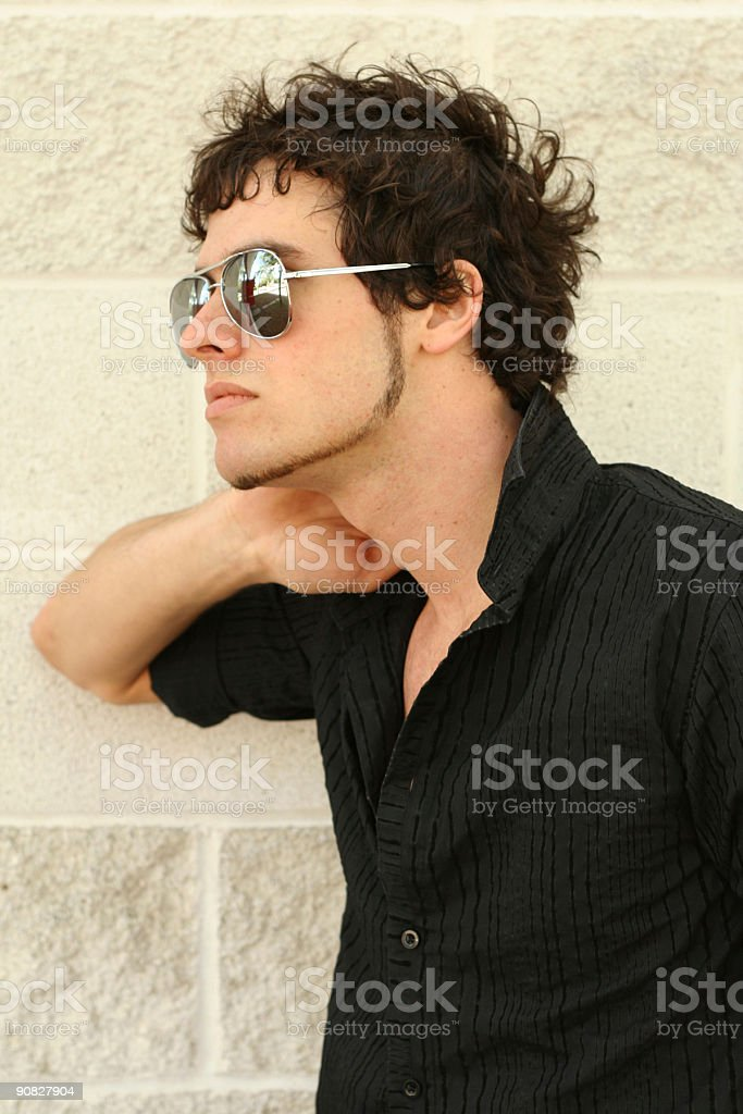 Young Man leaning against wall stock photo