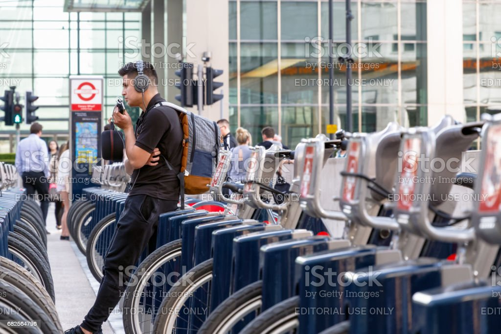 A young man leaning on a Santander bike at a docking station in Canary Wharf stock photo