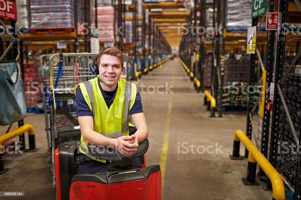 Young man leaning on tow tractor in distribution warehouse stock photo