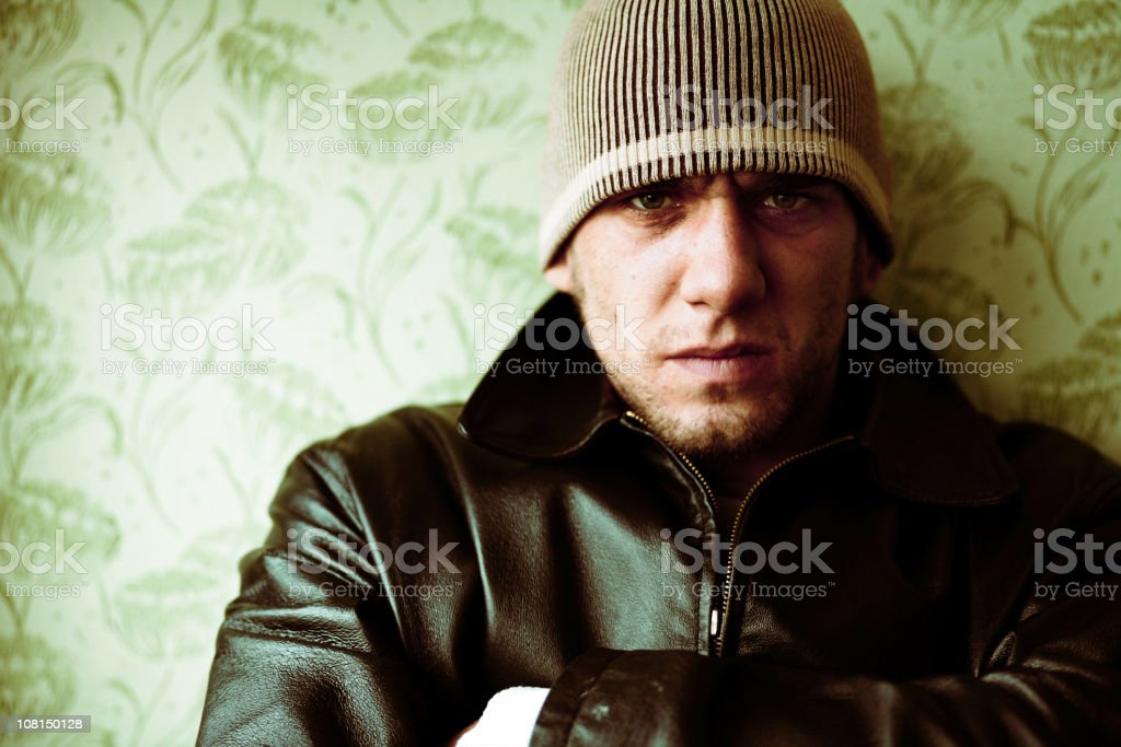 Young Man Leaning on Wall and Wearing Leather Jacket royalty-free stock photo
