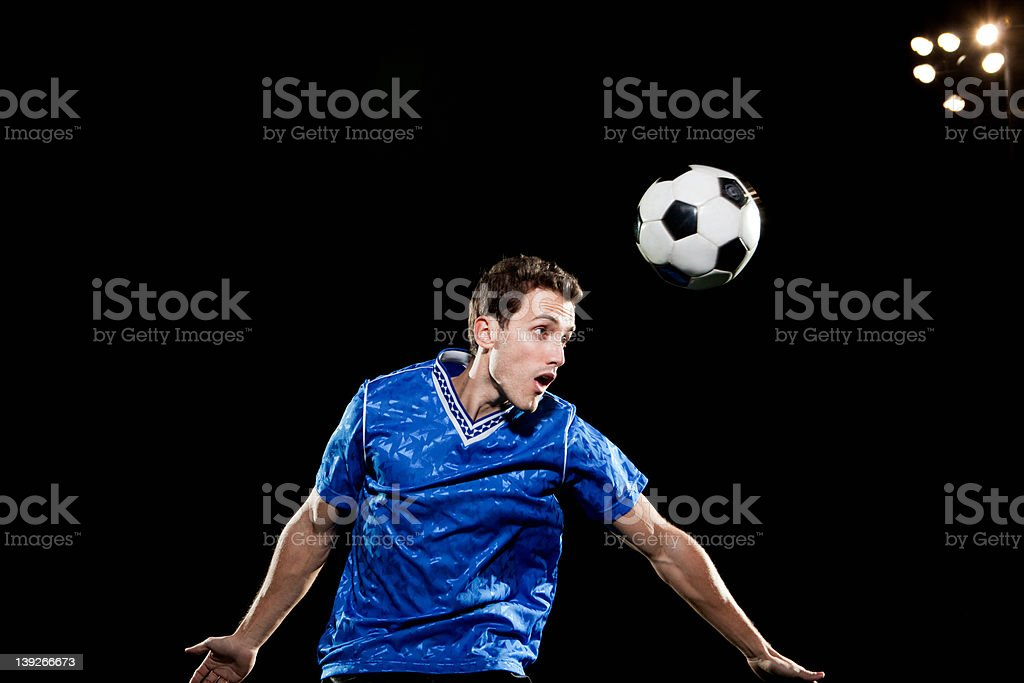 Young man leaping to head soccer ball stock photo