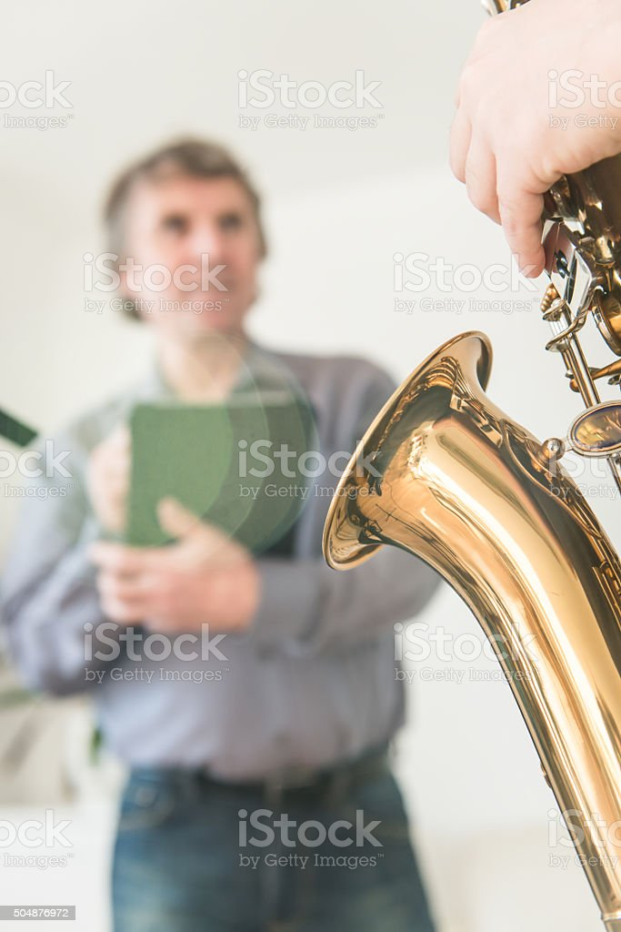 Young Man Learning to Play Saxophone at Home stock photo