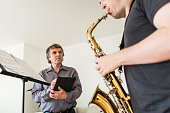 Young Man Learning to Play Saxophone at Home