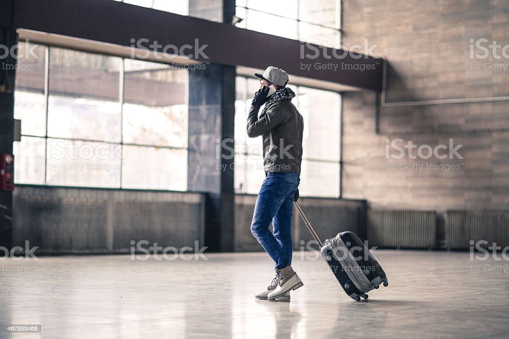 Young man leaving the station and talking on the phone. stock photo