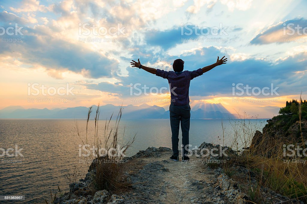 Young man lifting hands to the sky in worship stock photo