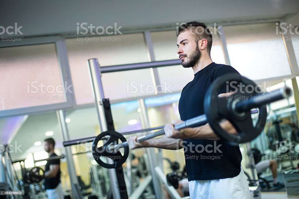 Young man lifting weights in a gym stock photo