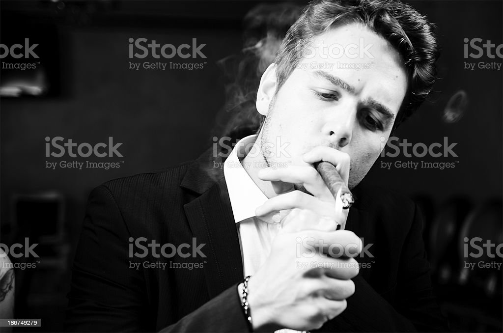 Young man lighting cigar like a boss royalty-free stock photo