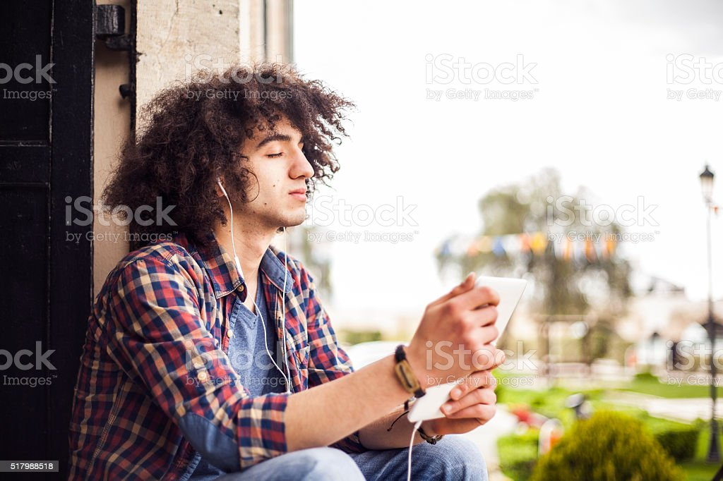Young man listening music with digital tablet stock photo