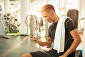 Young man listening to music after hard workout in gym.