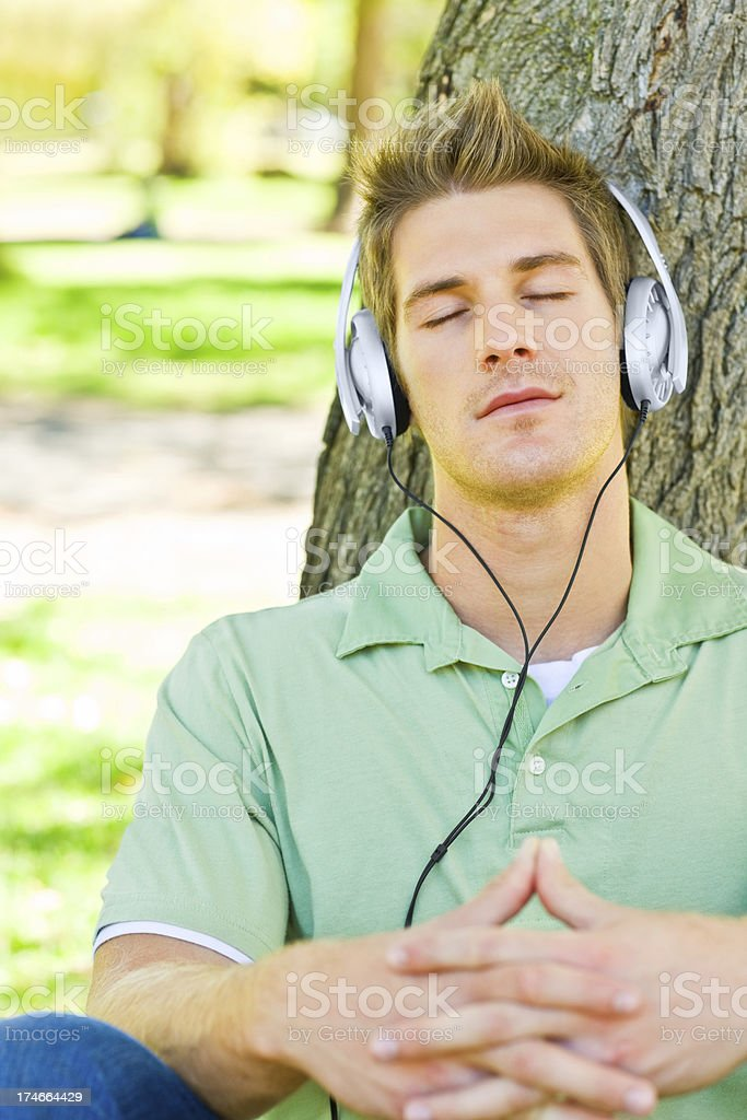 Young man listening to music at the park royalty-free stock photo