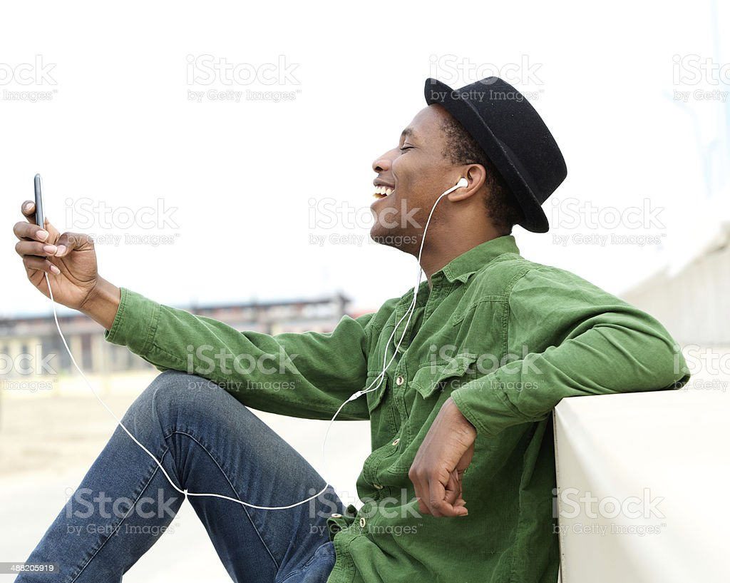 Young man listening to music on cellphone stock photo