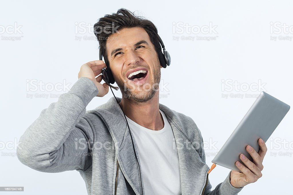 Young man listening to music on digital tablet royalty-free stock photo