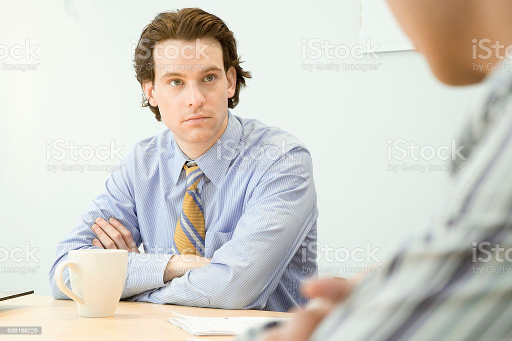 Young man listening to office colleague in meeting stock photo
