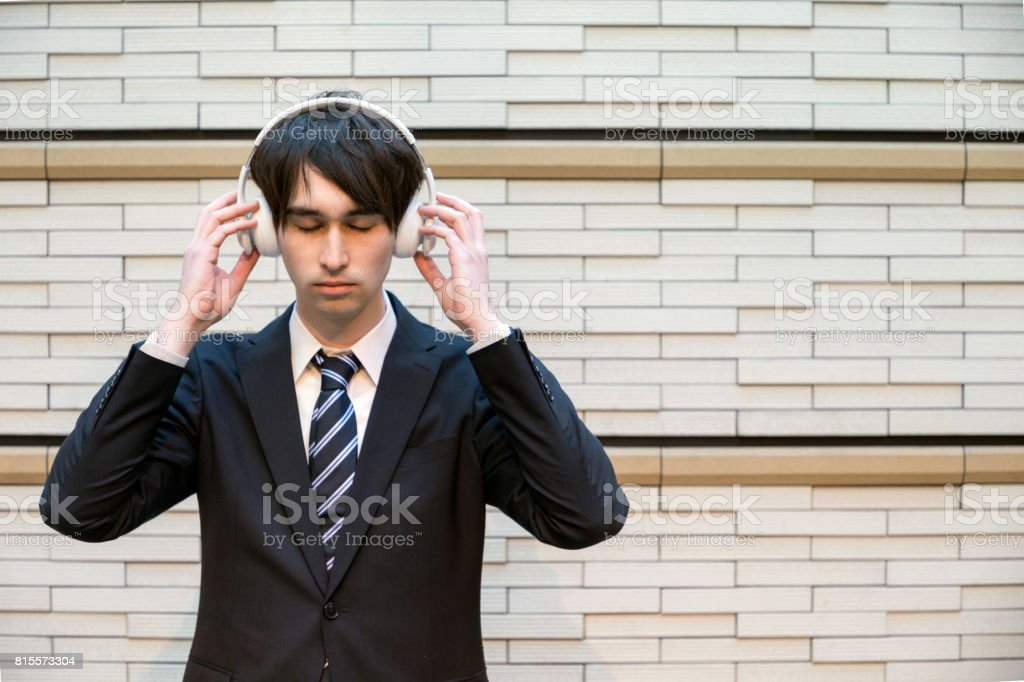 young man listening to the music with wireless headphone. stock photo