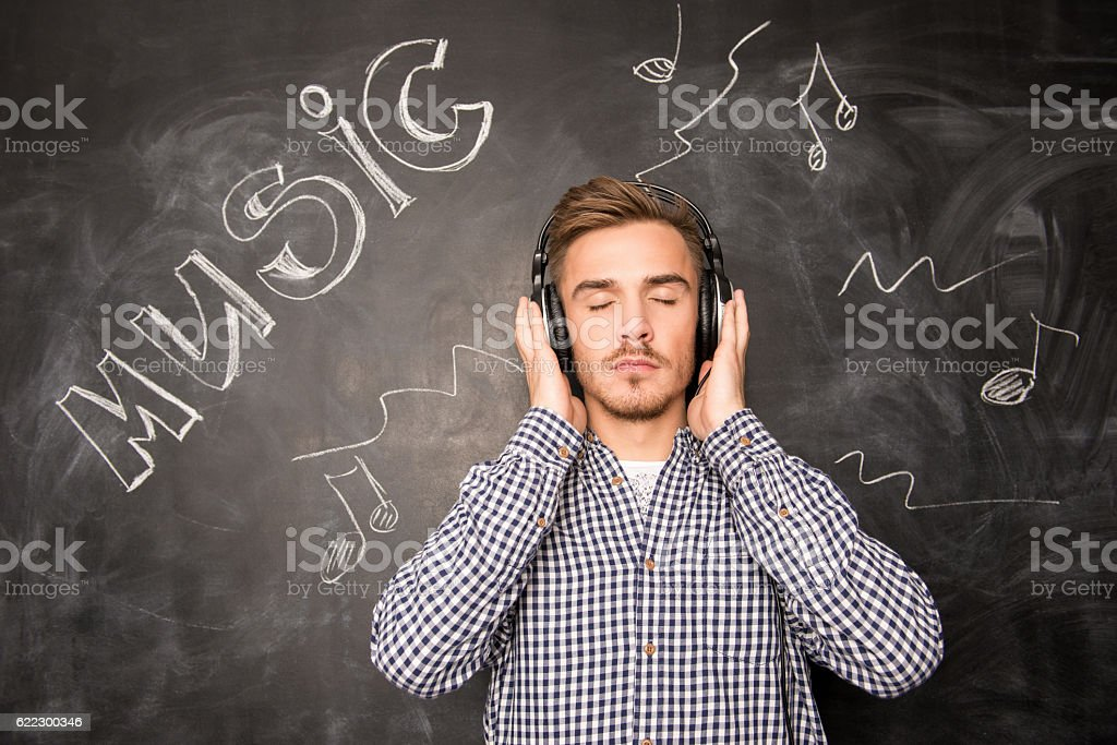 young man listens to music in headphones stock photo