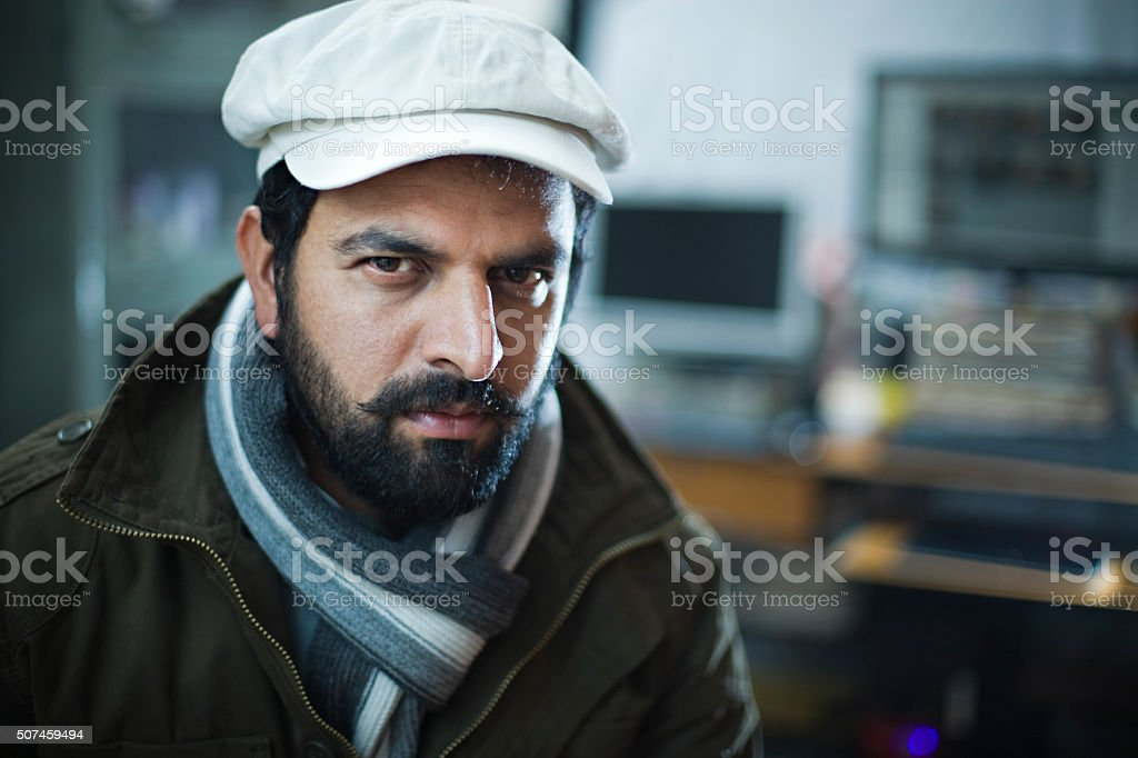 Young man looking at camera with blank expression. stock photo