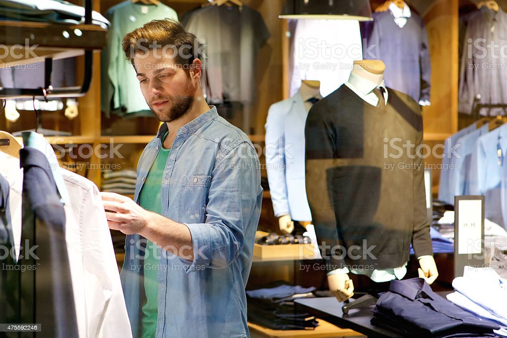 Young man looking at clothes to buy at shop stock photo