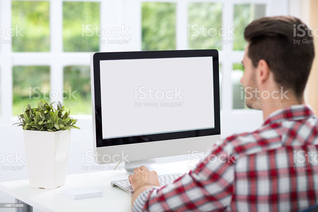 Young man looking at computer screen stock photo