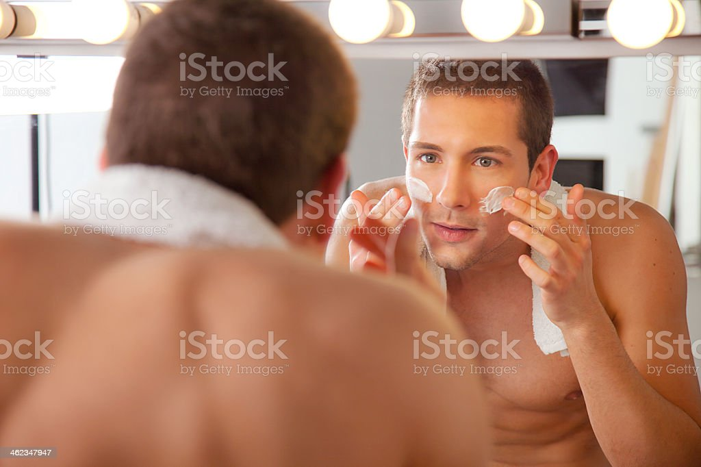 A young man looking at himself in a mirror stock photo