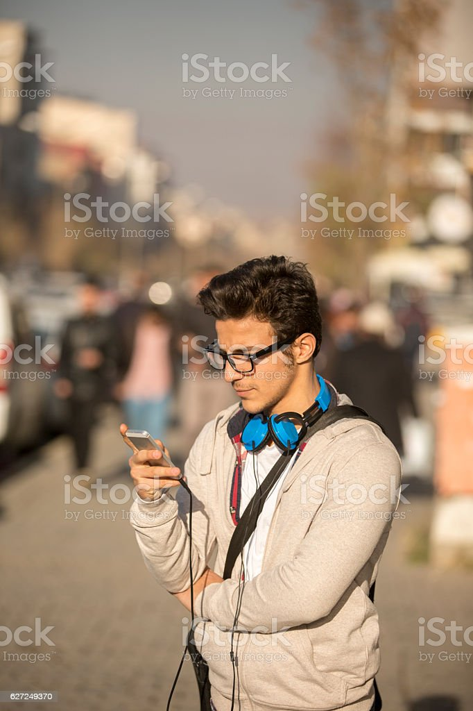 Young man looking at his smart phone outside stock photo