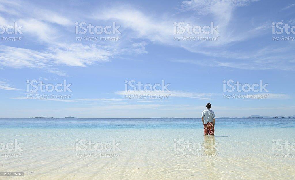 young man looking at horizon on tropical beach royalty-free stock photo