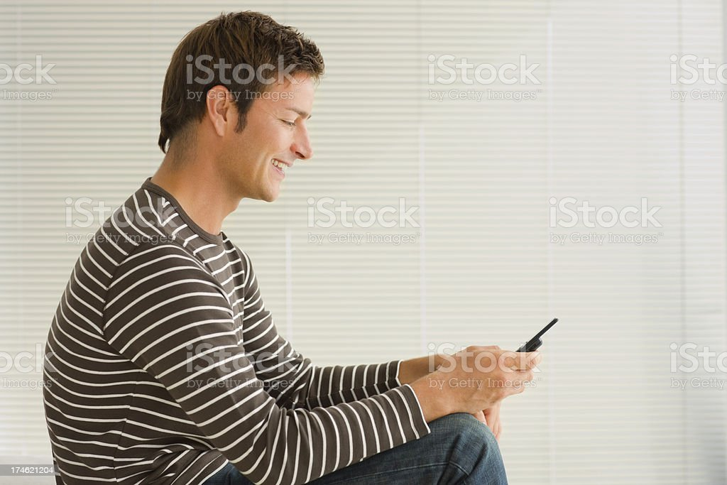 Young man looking at mobile phone royalty-free stock photo