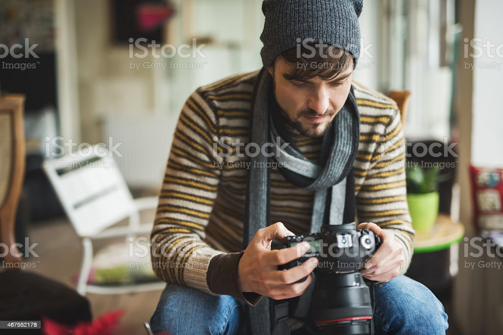 Young man looking at photos on digital camera. stock photo