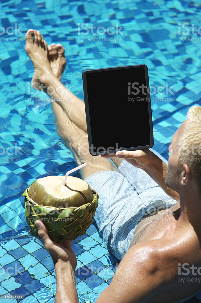 Young Man Looking at Tablet Computer Fresh Coconut in Pool stock photo