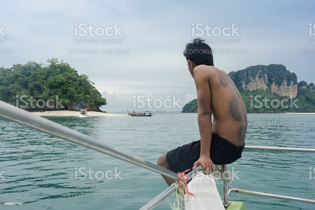 Young man looking at tourist boat in Krabi, Thailand photo libre de droits