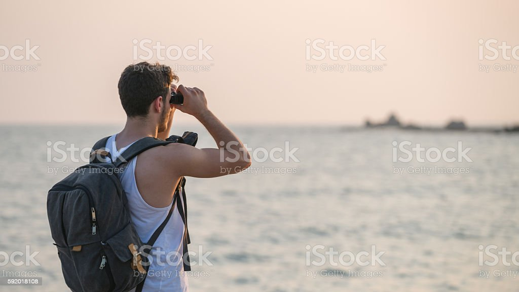 Young man looking far with Binoculars stock photo