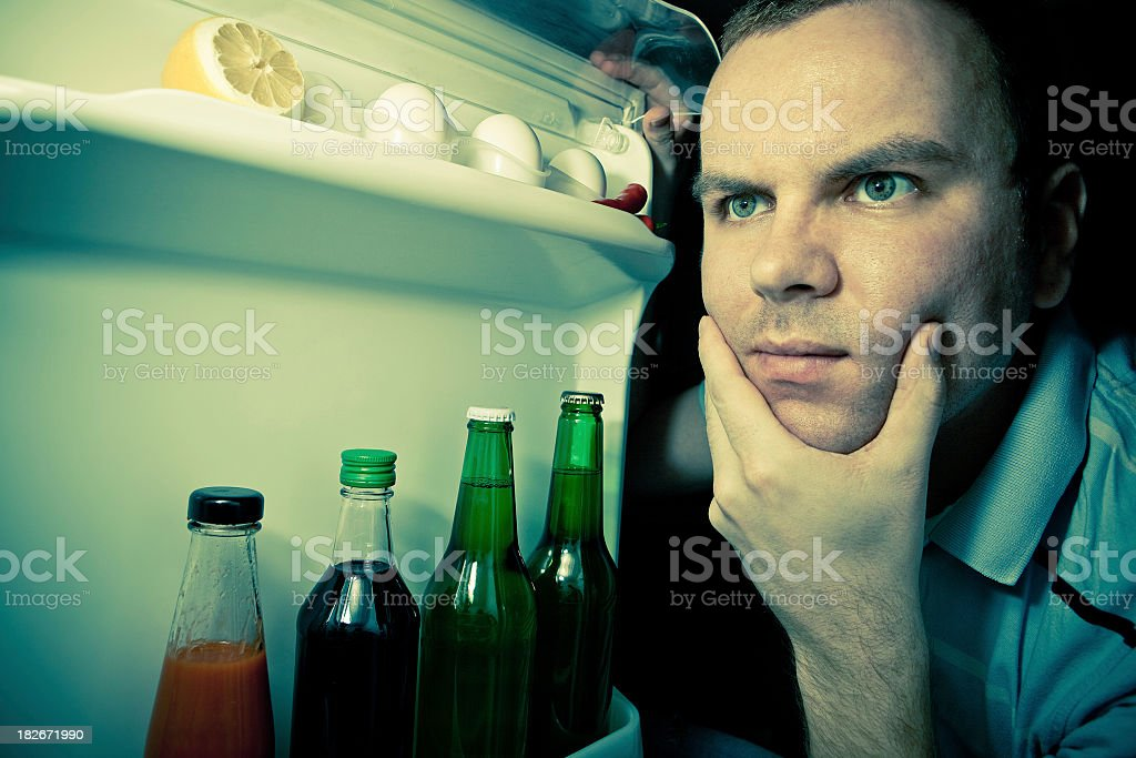 Young man looking for food in refrigerator royalty-free stock photo