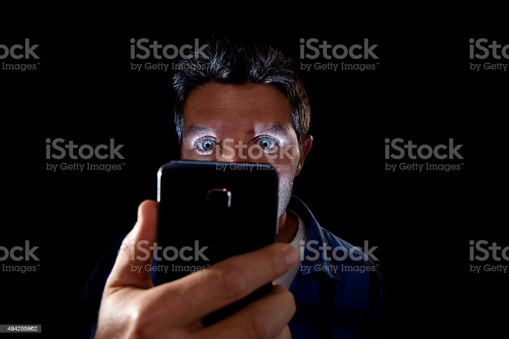young man looking intensively mobile phone screen stock photo