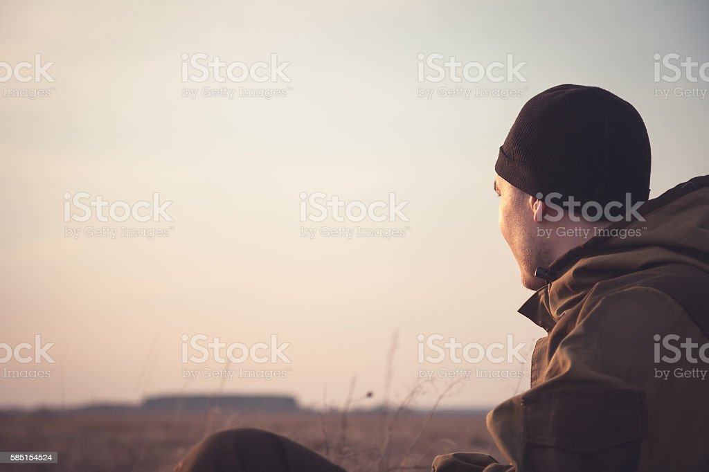 young man looking into the distance at dawn in field stock photo
