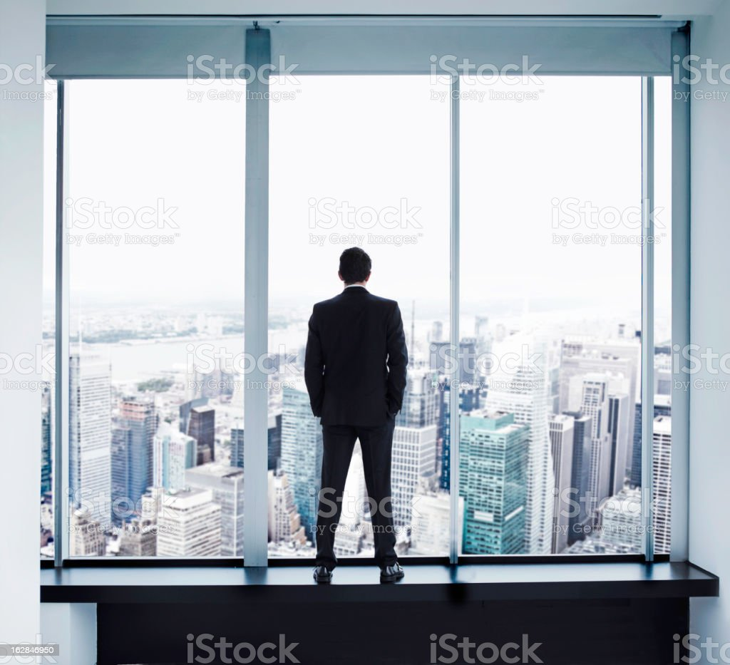 Young man looking out at Manhattan skyline stock photo