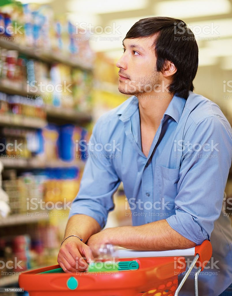 Young man looking out for goods at the supermarket royalty-free stock photo