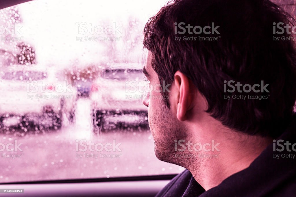 Young Man Looking Out Rainy Window at New Cars stock photo