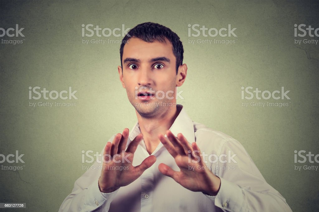 young man looking shocked scared trying to protect himself from unpleasant situation stock photo
