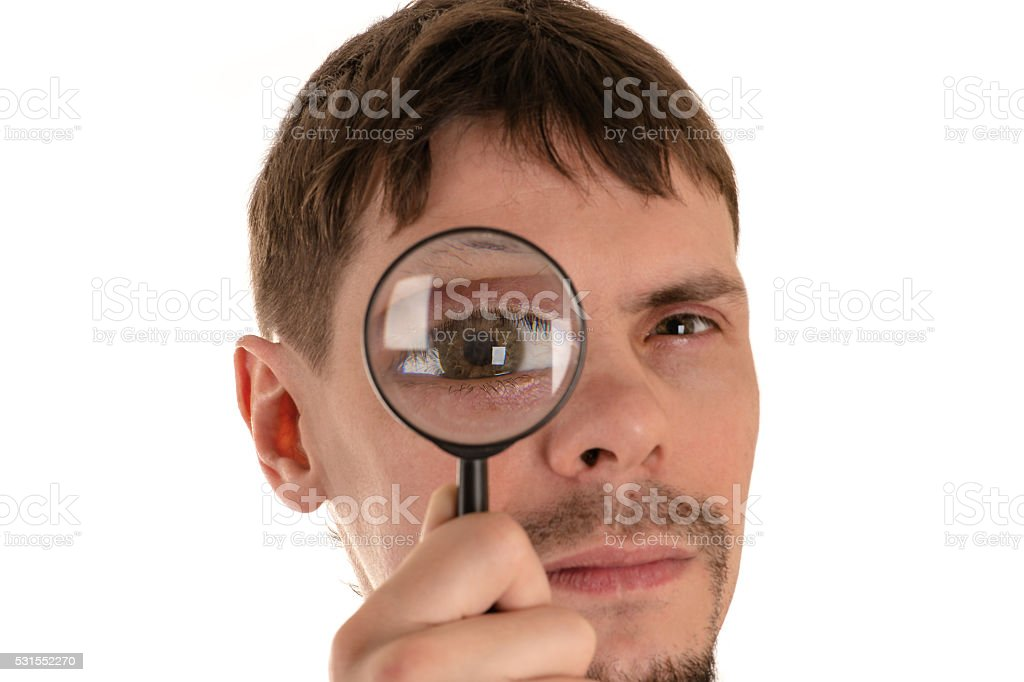 young man looking through a magnifying glass giant eye stock photo