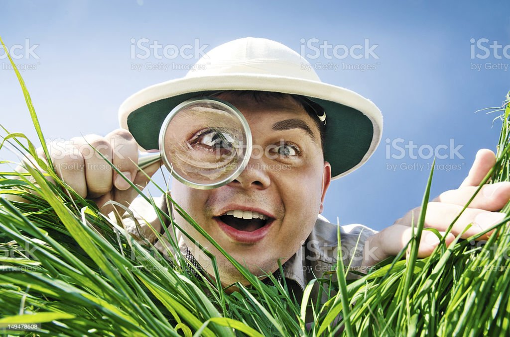 Young Man Looking through a Magnifying Glass stock photo